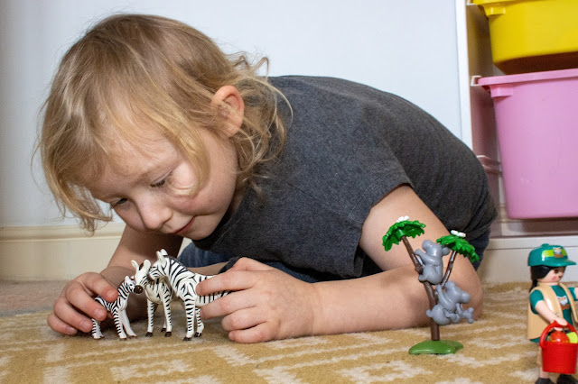 A 5 year old girl playing with a family of 3 zebras from Playmobil