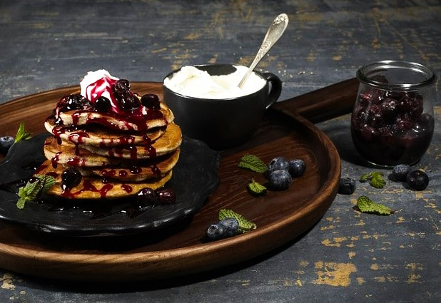 Wooden breakfast tray with stack of pancakes topped with blueberry compote and cream cheese