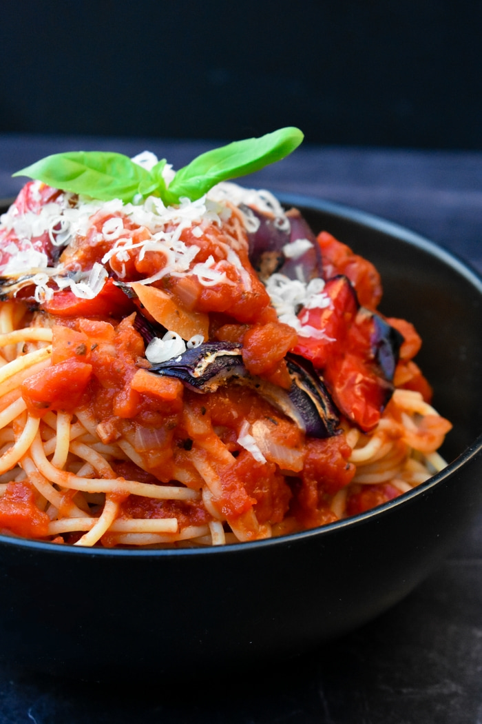 close up of a bowl of spaghetti with rich tomato sauce and roast red peppers and red onions