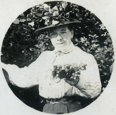 Rebecca Beck holding a small posy of flowers wearing a large brimmed hat with flowers