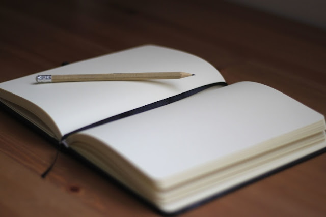 an open notebook with a pencil, ready to be written on
