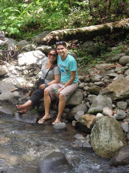 A couple relaxing in Vera Falls' stream in Albay