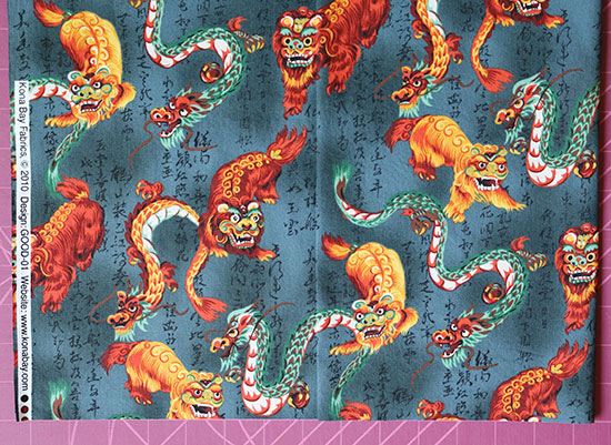 Dragon fabric folded on itself to show pattern alignment and straight cutting.