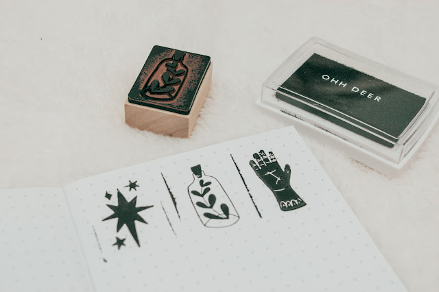3 used stamps and an ink pad with the stamps printed on a dotted notebook