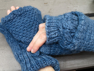 person wearing a pair of flip-top convertible mittens.  They are unbuttoning the left-hand mitten from the back of the hand.