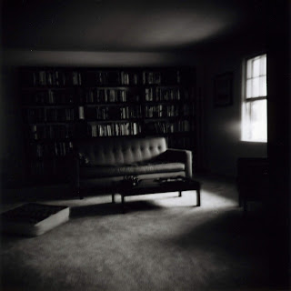 Black and white photograph of a sofa and coffee table lit by a window with a wall full of shelves of books behind