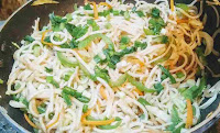 Prepared hakk noodles topped with chopped spring onions for hakka noodles veg recipe