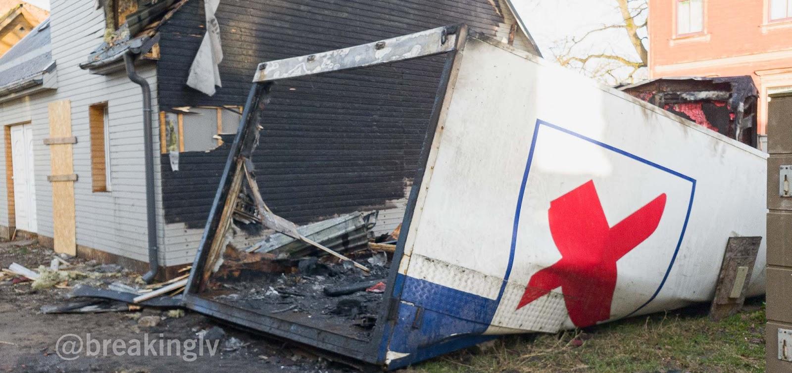 Liesmās nopostīts konteiners un koka ēkas siena
