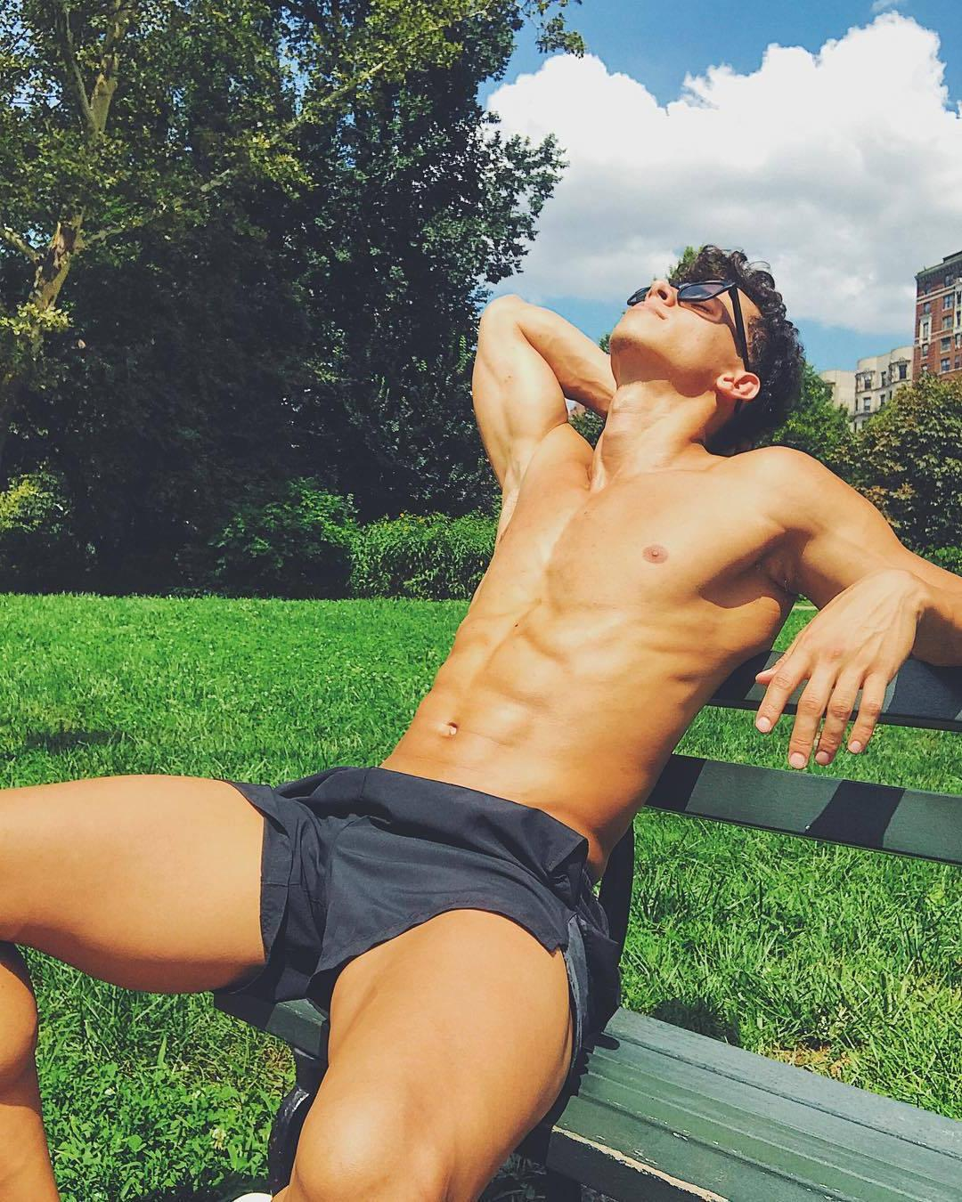 shirtless-fit-abs-young-boy-next-door-curly-hair-enjoying-sunglasses-tanning-outside-park