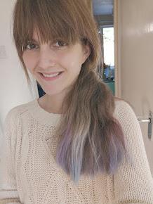 A caucasian woman with brown hair and purple hair wearing a  cream jumper