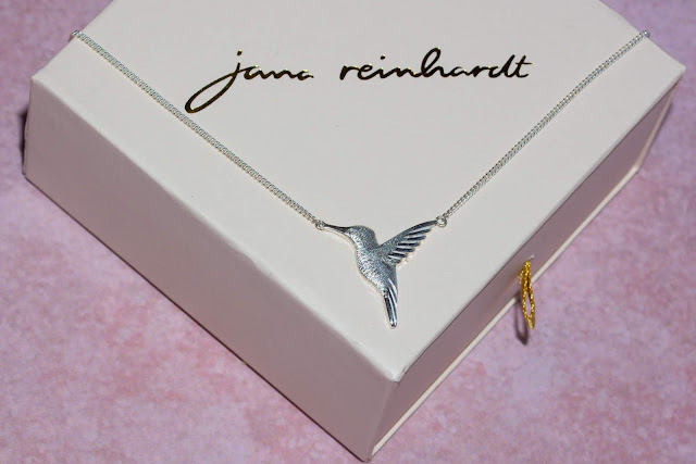 Silver hummingbird necklace on packaging for giveaway prize
