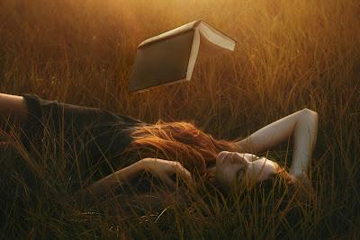 Linda chica acostada en el campo con un libro volando