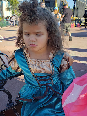 A curly haired girl in a teal and gold dress, pouting.