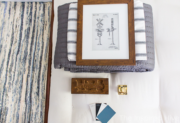 Bedding, vintage train art, paint swatches, and brass hardware on mattress from The Futon Shop