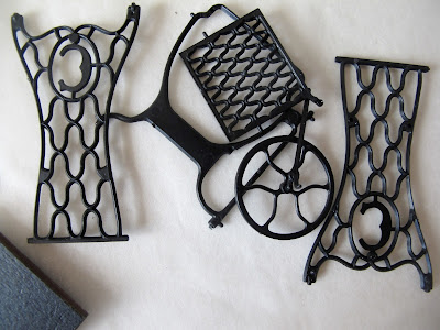 Pieces of a dolls' house miniature treadle sewing machine kit strewn on a tabletop.