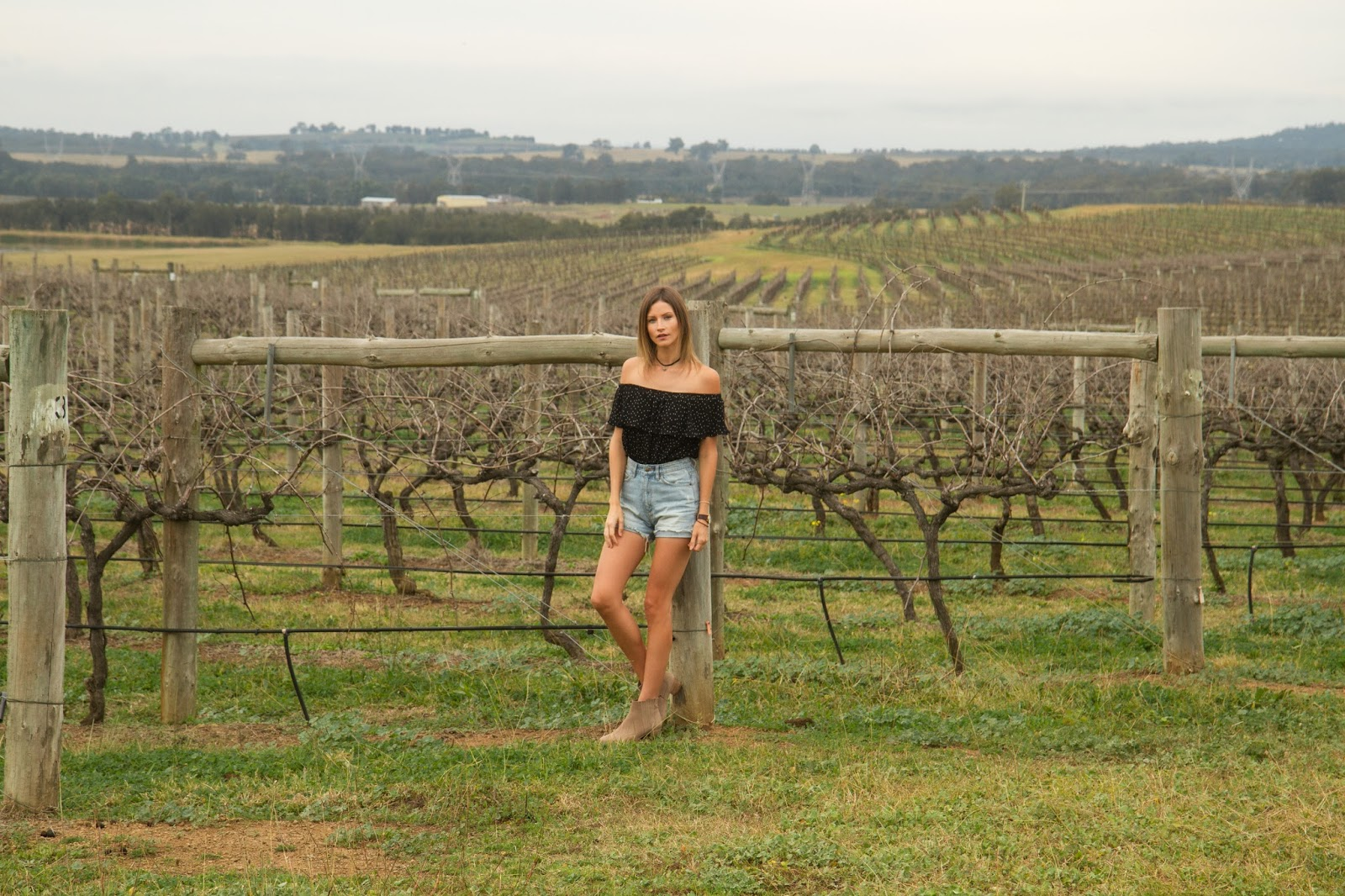 Fashion and travel blogger, Alison Hutchinson, is wearing a Topshop Bardot top, Ksubi denim shorts and Witchery beige ankle boots in the Hunter Valley, Australia
