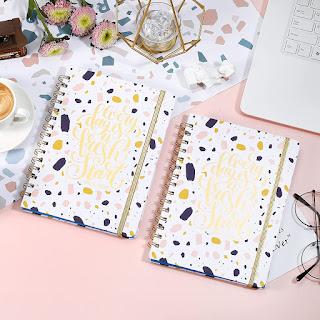 Agenda blanca con manchas de colores y letras en doradas.