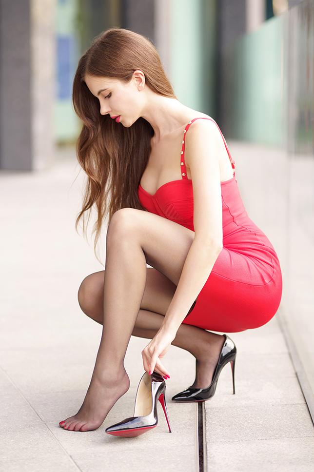 Czerwona sukienka, czarne cienkie rajstopy i lakierowane szpilki