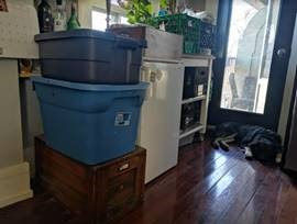 Two plastic bins used as indoor worm composters stacked on top of each other in a kitchen.