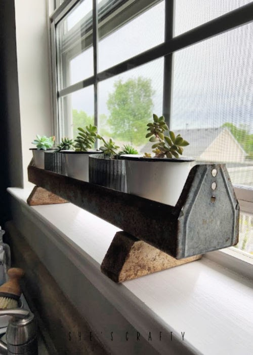 New uses for vintage goods in home decor  |  chicken feeder to hold plants and succulents