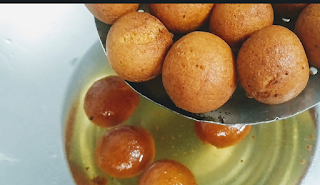 Dipping fried gulab jamun into sugar syrup