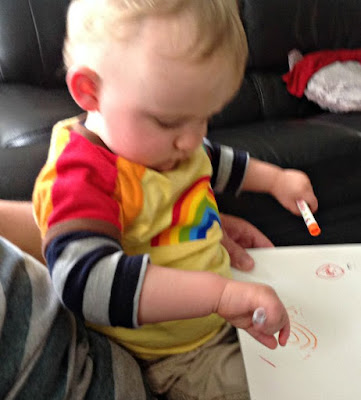 baby holding pens in his hands and scribbling on white paper