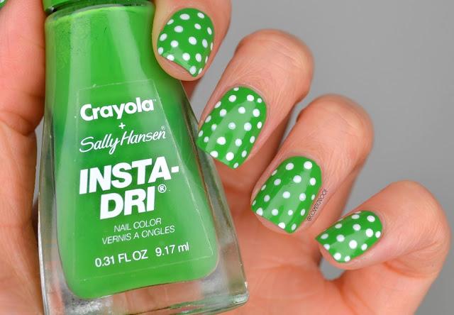 green polka dot nail art holding green nail polish bottle