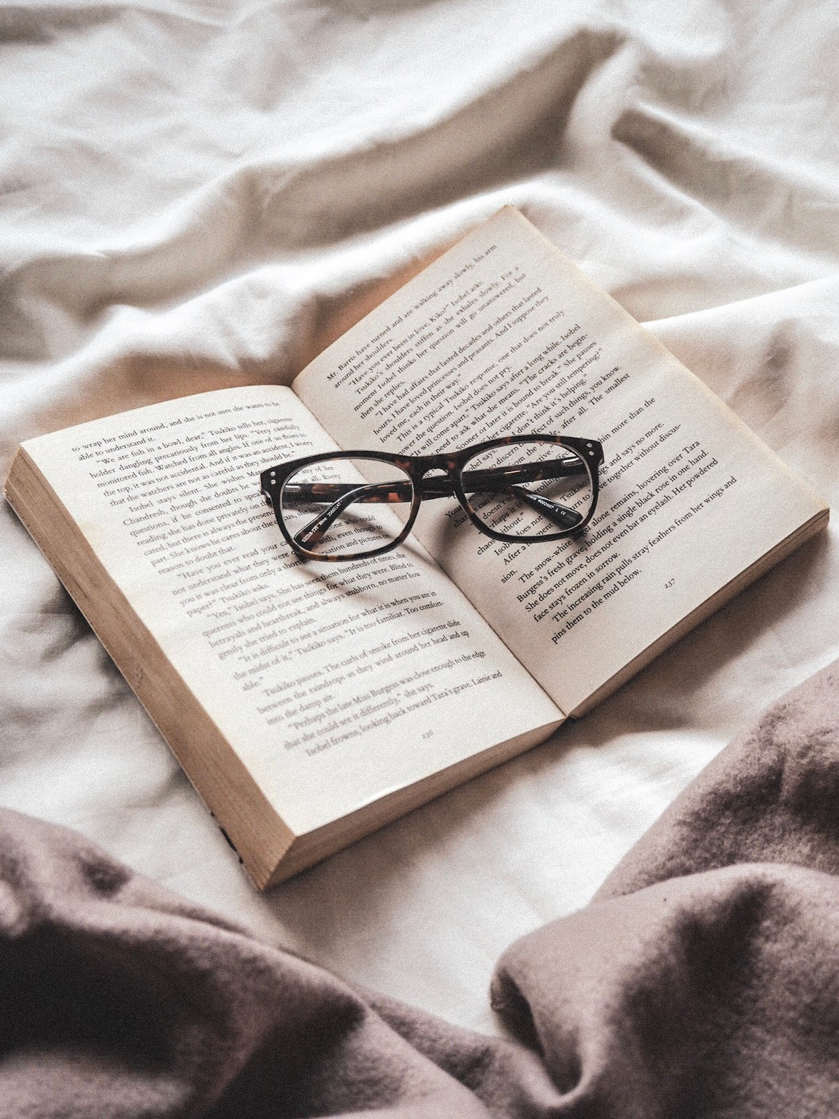 A flatlay of a open book placed on a white bed sheet with brown reading glasses on top and a brown throw peeking out from the left corner
