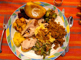 photo of a typical Thanksgiving dinner plate of mashed potatoes, stuffing, turkey, and vegetable sides
