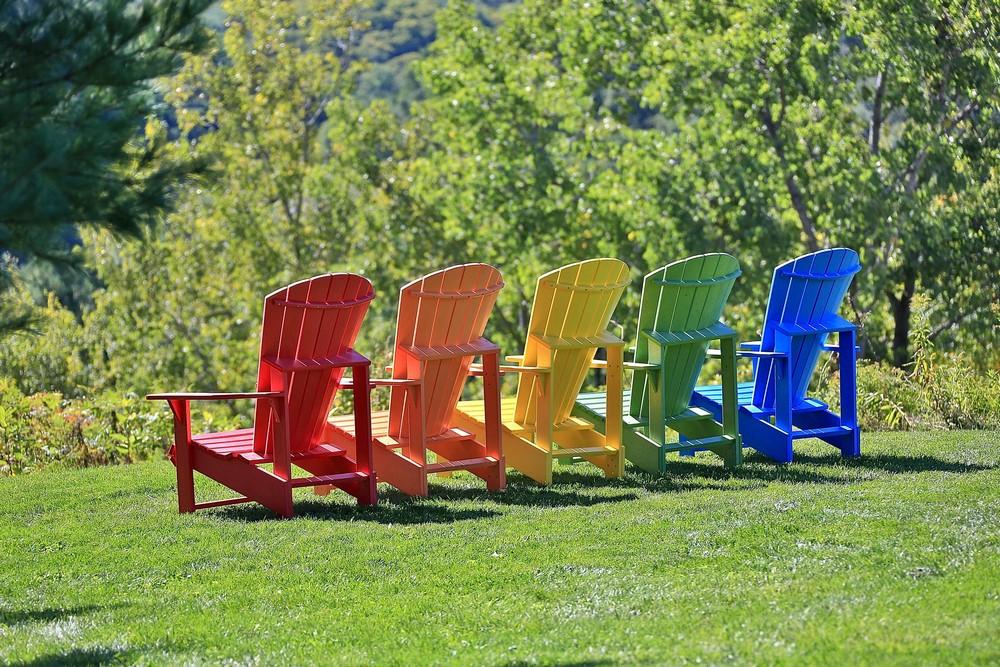 sillas de madera Adirondack en colores rojo, naranja, amarillo, verde y azul