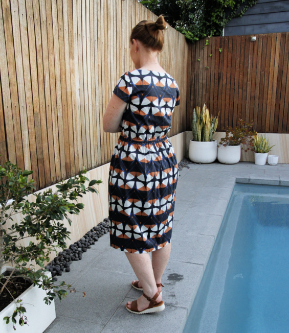 a photo showing the back of a woman standing next to a pool in a blue and orange print dress