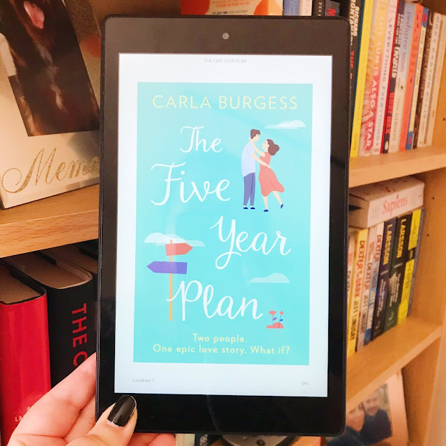 The Five Year Plan by Carla Burgess on kindle held up in front of bookshelf