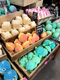 A selection of spherical and square bath bombs in rectangular light brown boxes with rectangular black tags next to them which say words including, Golden Wonder, Fireball, Snowman Dreaming in white font on a bright background