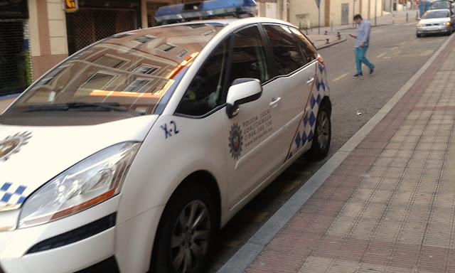 Uno de los coches patrulla, estacionado ante la comisaría