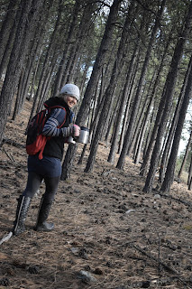 Alexia, with a black and red Underarmor backpack and mug and Coffee thermos, heading into the pine tree woods for a day of writing.