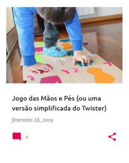 Criança a brincar num tapete feito de cartão, com desenhos de pés e de mãos