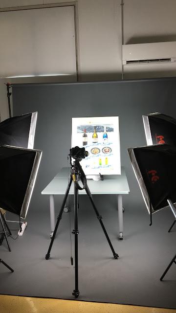 Kuvassa museoesineiden kuvauspiste, pöydän päällä on kehystetty juliste, pöydän ympärillä neljä kuvausvalaisinta ja kamera jalustalla.
