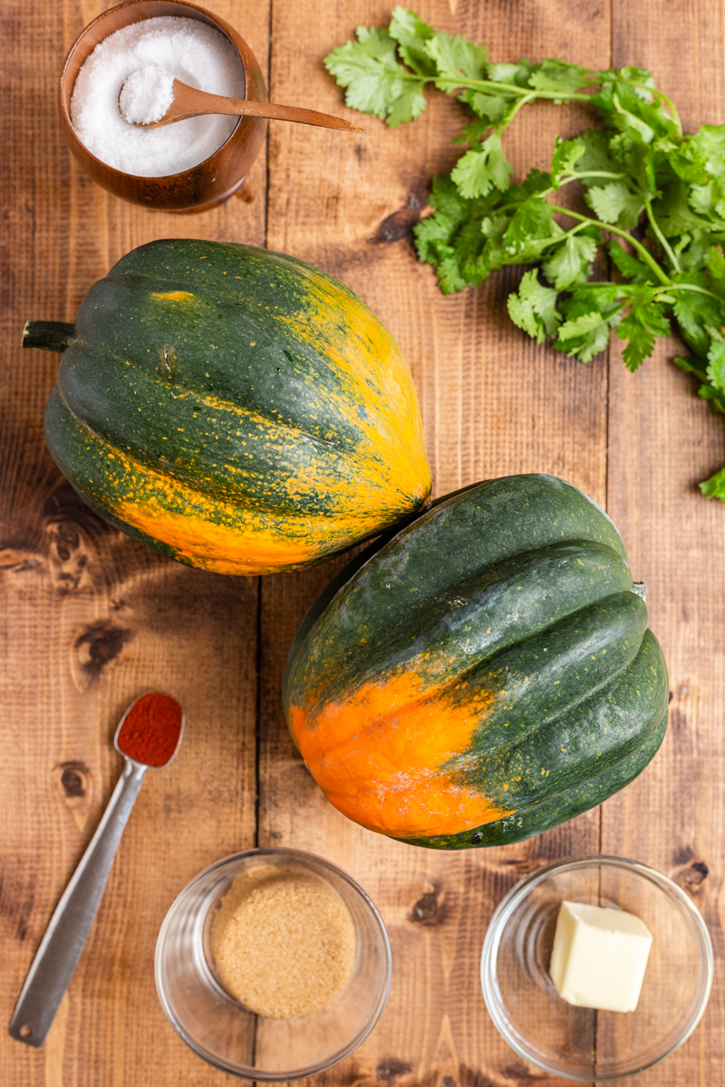 Photo of ingrdients to make Low Carb Brown Sugar Chile Roasted Acorn Squash on a wooden table.