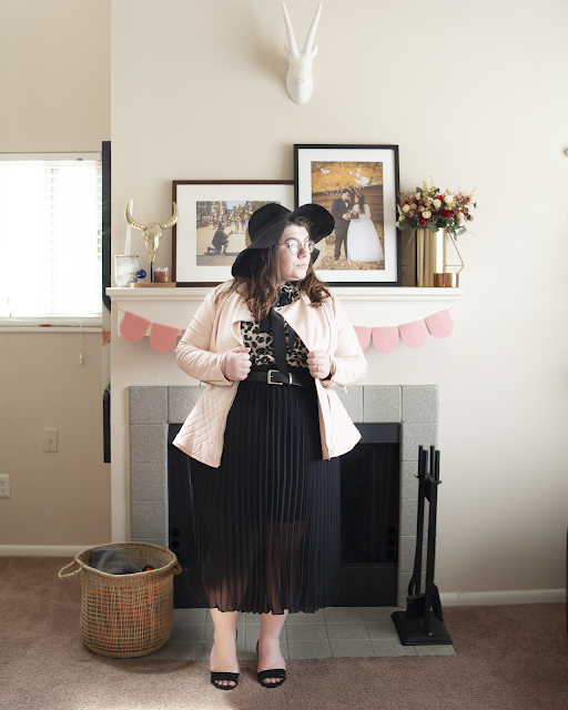 An outfit consisting of a black wide brim hat, animal print blouse with attached black bow, pink faux leather jacket, black pleated midi skirt and black peeptoe shoes.