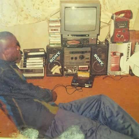 """Caption this photo of a young man feeling his """"well-furnished"""" sitting room in 1997"""