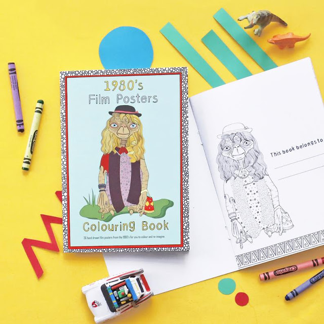 An A5 colouring book showing a line illustration of ET from the scene when he is dressed in women's clothes and wig. Around the book are toy cars and crayons.