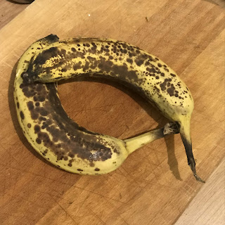 Two ripe bananas lying on a kitchen worktop.