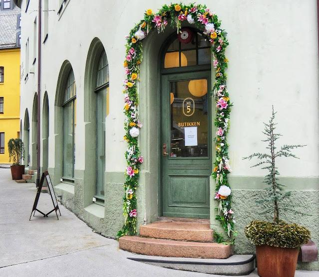 Green Art Nouveau door with floral trim in Alesund Norway