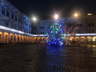 christmas tree and snowflake projections on the side of a castle