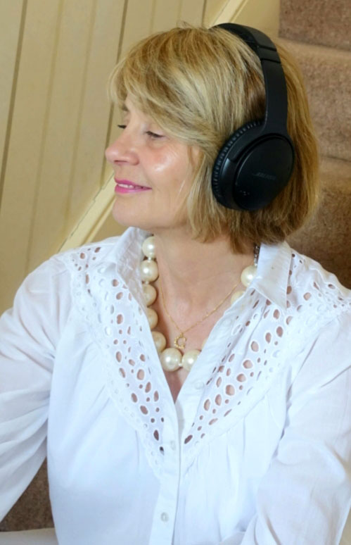 UK blogger Gail Hanlon from Is This Mutton with headphones on enjoying a podcast or two