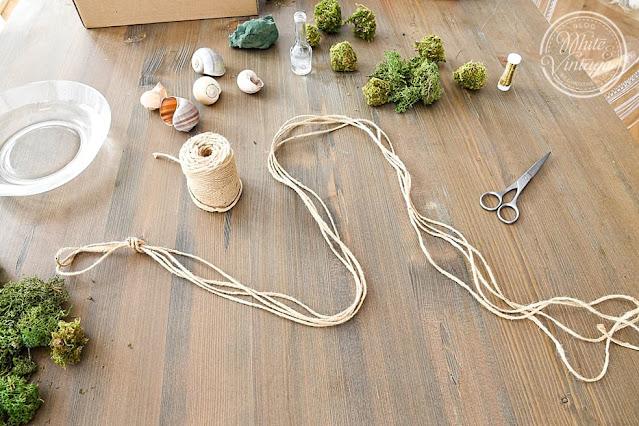 Materialien für eine Girlande aus Schneckenhäusern und Blumen.