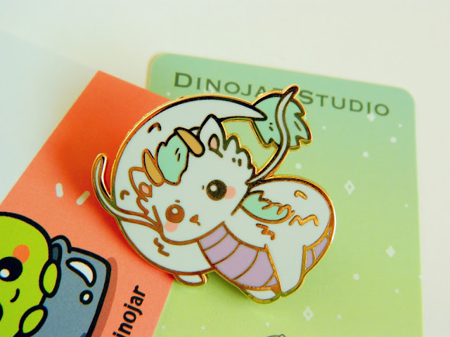 A photo of an enamel pin, the character is dragon haku from the Studio Ghibli movie, Spirited Away. He is white, purple and mint in colour and has a cute solemn expression.