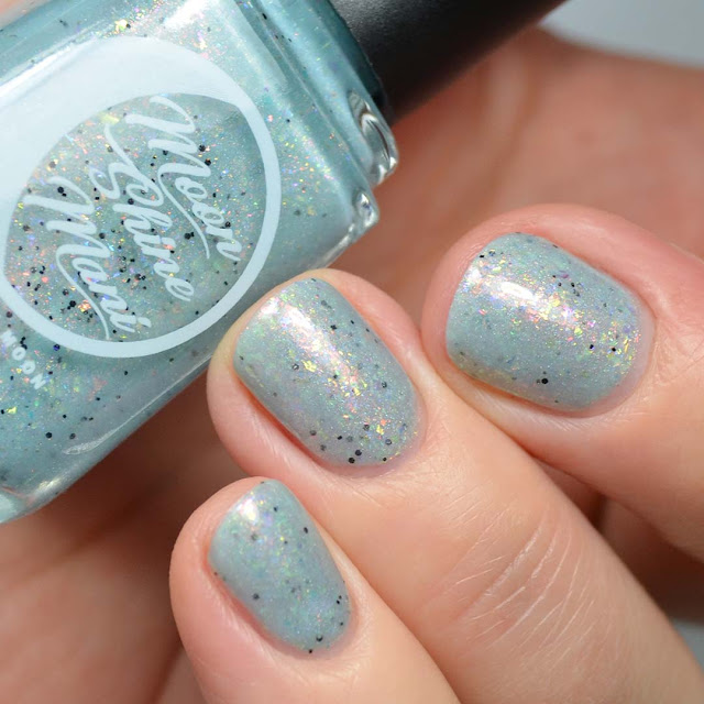 blue nail polish with color shifting flakies and black glitter swatch
