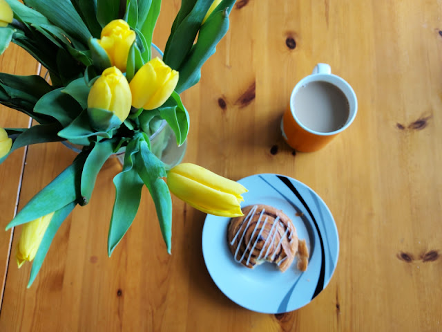 Yellow tulips, a cinnamon swirl on a black and white plate and a cup of tea on a wooden table