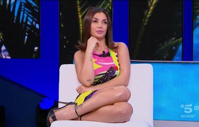 Elettra Lamborghini foto seduta sul divanetto scarpe vestito colorato Isola dei famosi 5 aprile